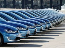 People walk pasta row of Volkswagen e-Golf cars during the company's annual news conference in Berlin