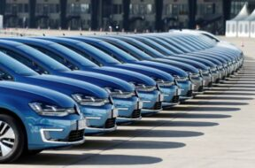 People walk past a row of Volkswagen e-Golf cars during the company's annual news conference in Berlin