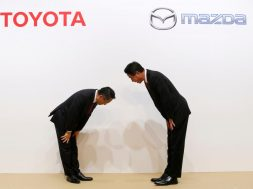 Toyota Motor President Akio Toyoda and Mazda Motor President Masamichi Kogai bow at a joint news conference in Tokyo