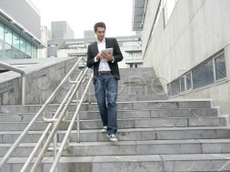 man-walking-down-stairs-tablet-footage-014830136_prevstill