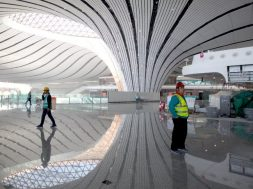 Construction workers are seen inside the terminal hall of the Beijing Daxing International Airport under construction in Daxing district, Beijing