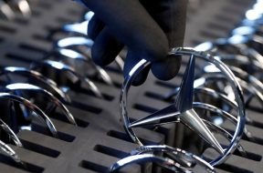 FILE PHOTO: An employee of German car manufacturer Mercedes Benz prepares the company's logo prior to its installation at the A-class production line at the Daimler factory in Rastatt