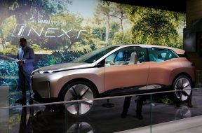 FILE PHOTO: Man stands next to a BMW's Vision iNEXT displayed during the media day for Shanghai auto show